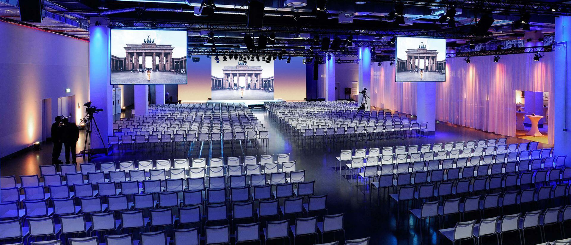 reef berlin event area with blue lighting and set seating with a screen